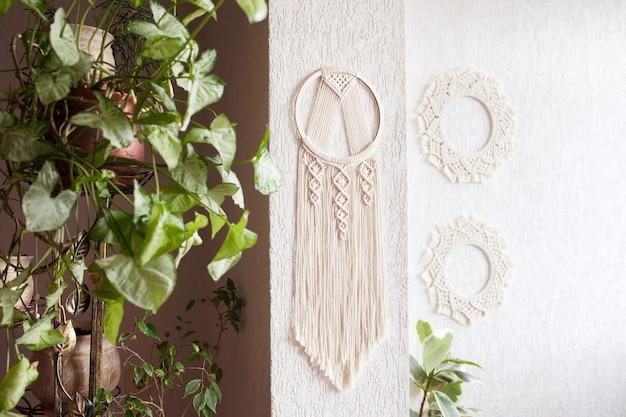 Apanhador de sonhos de macramé de algodão feito à mão no fundo branco da parede. amuleto tradicional para proteger o sono. renda macramê na parede com folhas verdes