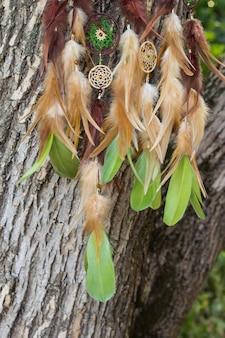 Apanhador de sonhos feito à mão com fios de penas e contas penduradas em corda
