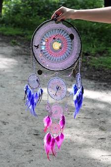 Apanhador de sonhos feito de penas, couro, miçangas e cordas