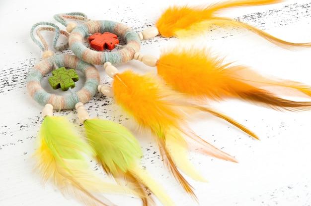 Apanhadores de sonhos brilhantes com cruzes laranja e verdes