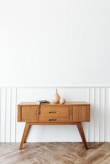 Aparador de madeira com livros e um vaso