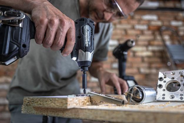 Aparafusar um parafuso autorroscante em um orifício de fixação de metal em uma tira de madeira usando uma chave de fenda, trabalho de um carpinteiro.