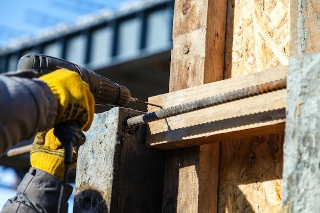 Aparafusar um parafuso em uma placa de madeira, close-up