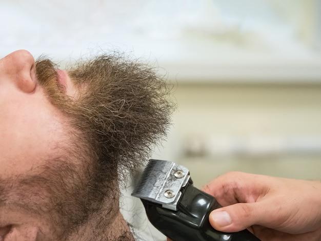 Aparar a barba com tesoura em uma barbearia. fechar-se.