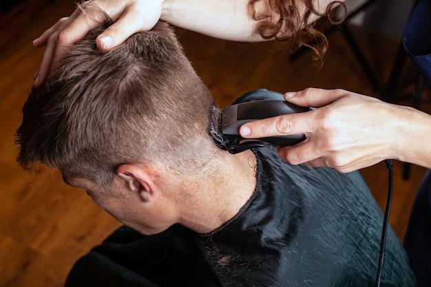 Aparar o cabelo com um aparador na parte de trás da cabeça