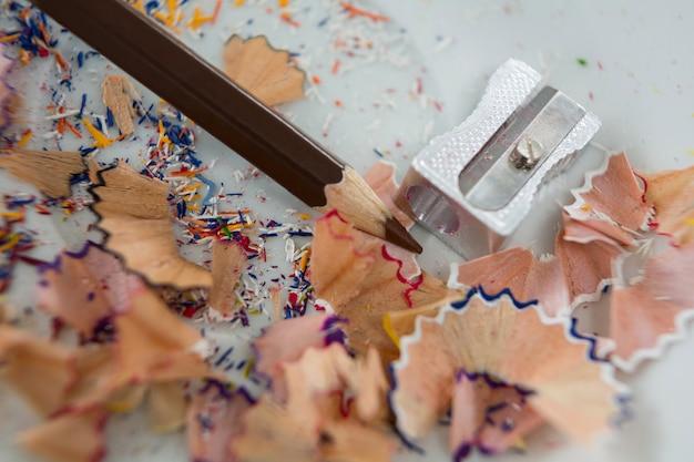 Aparas coloridas com lápis de cor marrom e apontador em pires
