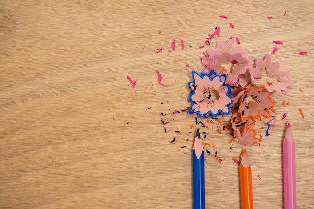 Aparas coloridas com lápis de cor na mesa de madeira
