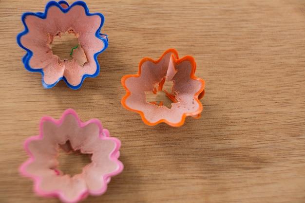 Aparas de lápis coloridos em forma de flor na mesa de madeira