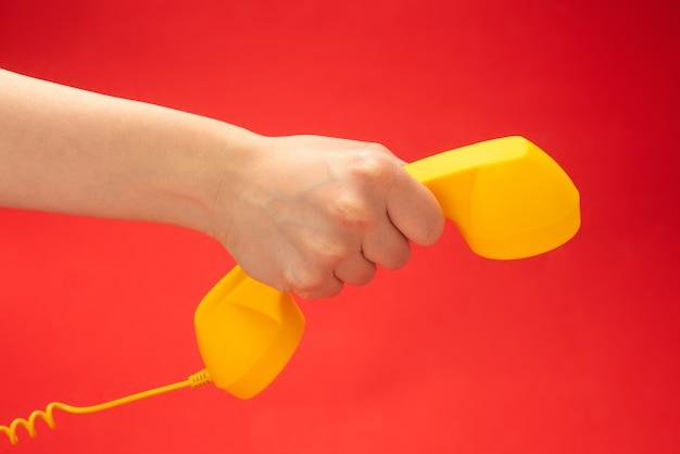 Aparelho amarelo na mão da mulher.