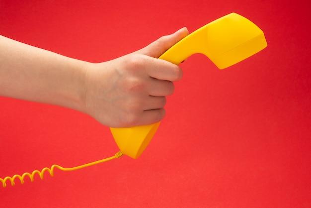 Aparelho amarelo sobre um fundo vermelho na mão da mulher