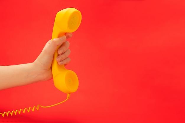 Aparelho amarelo sobre um fundo vermelho na mão da mulher.