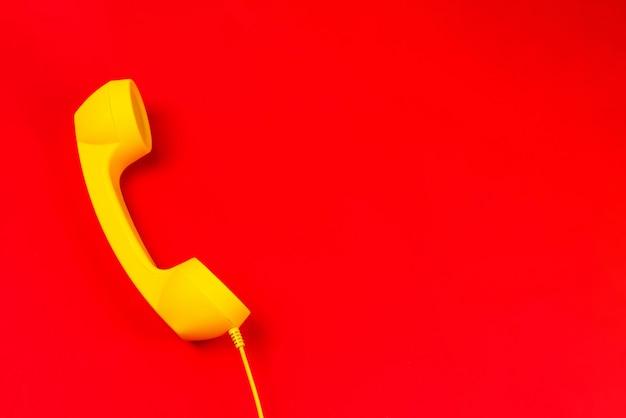 Aparelho amarelo sobre um fundo vermelho.