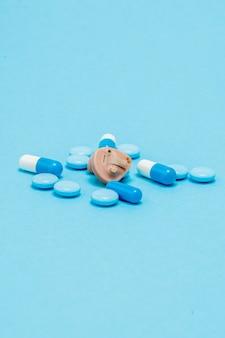 Aparelho auditivo e pílulas azuis em azul