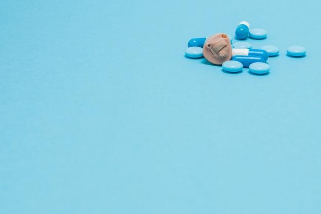 Aparelho auditivo e pílulas azuis sobre azul. conceito médico, farmacêutico e de saúde