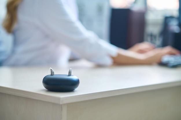 Aparelho auditivo na mesa e médico trabalhando no laptop