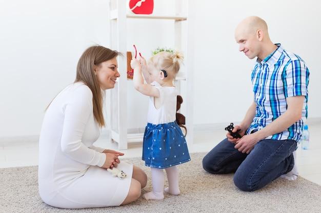 Aparelho auditivo no ouvido da menina. criança da criança usando um aparelho auditivo em casa.