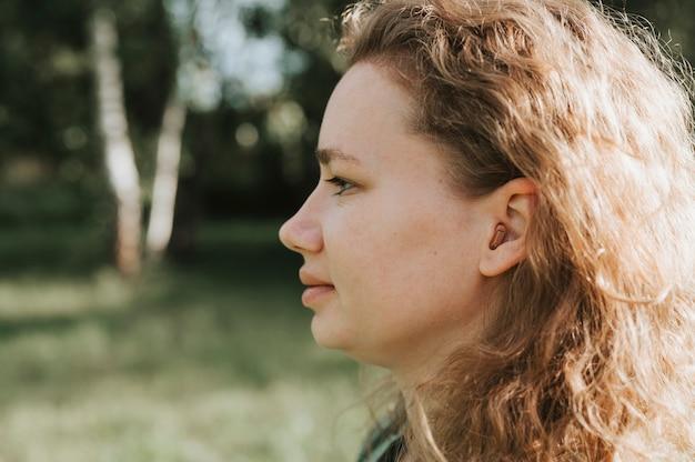 Aparelho auditivo pequeno intracanal no ouvido de uma mulher