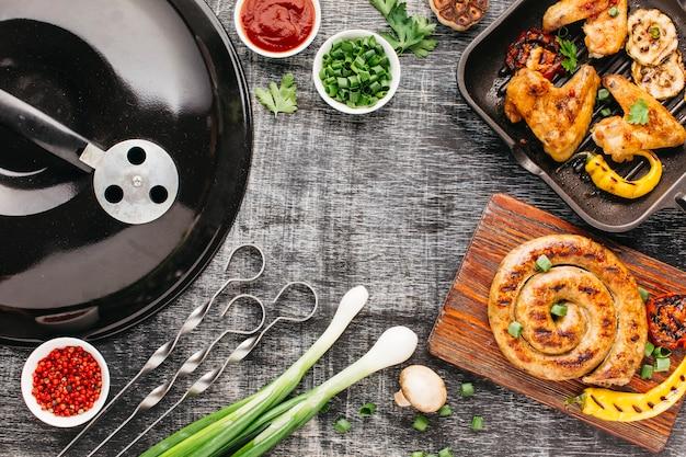 Aparelho de churrasco e carne grelhada em fundo de madeira