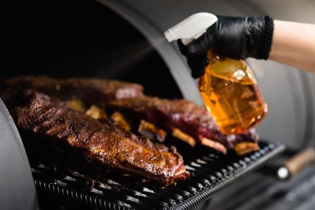Aparelho de cozinha profissional. closeup de costelas de carne de porco cozidas no fumante de churrasco. foto recortada do chef pulverizando carne grelhada.