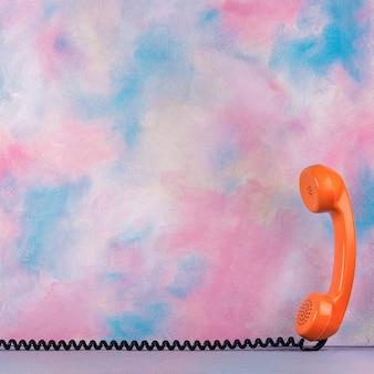 Aparelho de telefone vintage laranja em cima da mesa