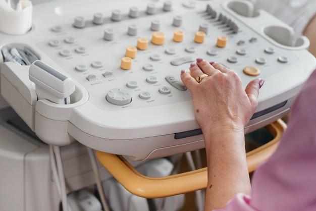 Aparelho de ultrassom close-up durante um exame médico de uma mulher grávida. exame médico