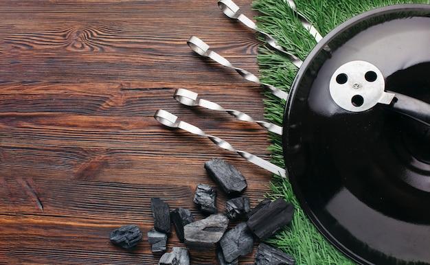 Aparelho de utensílio de churrasco com tapete de grama na mesa de madeira