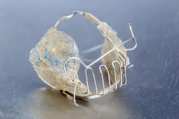 Aparelho dentário cinza ou retentor para dentes na parede metálica