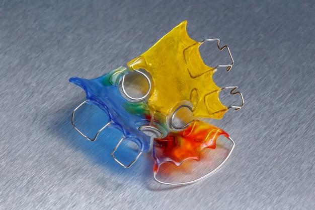 Aparelho dentário colorido ou retentor para dentes em fundo metálico, close-up