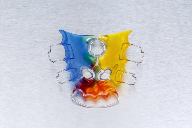 Aparelho dentário colorido ou retentor para dentes na parede de metal