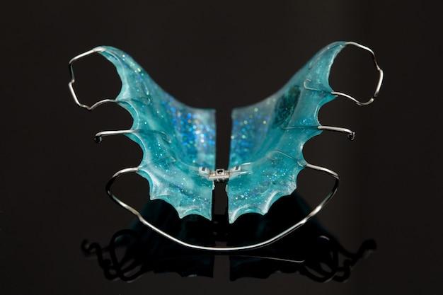 Aparelho dentário colorido ou retentores para dentes em fundo de vidro preto, close-up