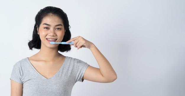 Aparelho dentário de uma adolescente asiática usando aparelho dentário e lentes de contato, ela muito confiante e orgulhosa se apresenta e sorri na parede branca adolescente de felicidade sorrindo