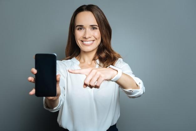 Aparelho eletrônico. mulher bonita bonita e alegre segurando seu smartphone e sorrindo enquanto aponta para ele