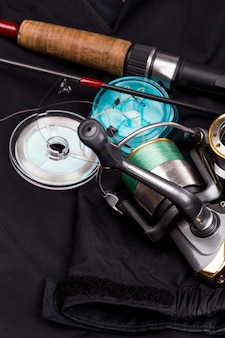 Aparelhos de pesca na jaqueta preta