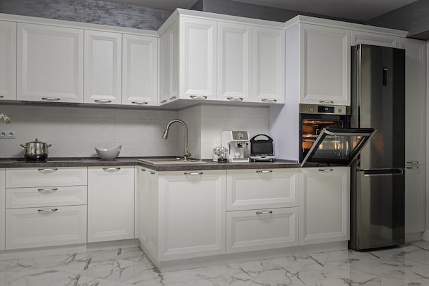 Aparelhos elétricos no interior minimalista da cozinha branca