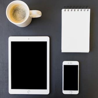 Aparelhos tecnológicos, caderno e café