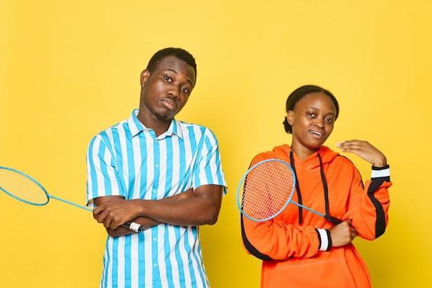 Aparência africana do jovem casal com raquete de tênis