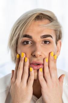 Aparência de maquiagem masculina e unhas amarelas