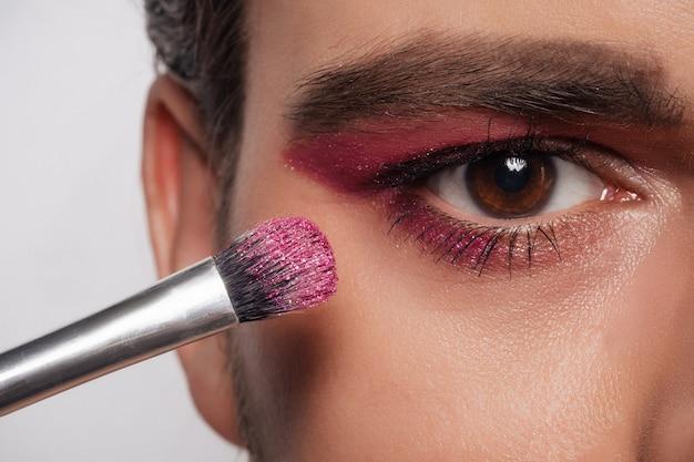 Aparência de maquiagem masculina. retrato de close-up de um jovem barbudo com um pincel de maquiagem