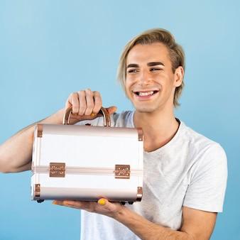 Aparência de maquiagem masculina segurando uma caixa de cosméticos