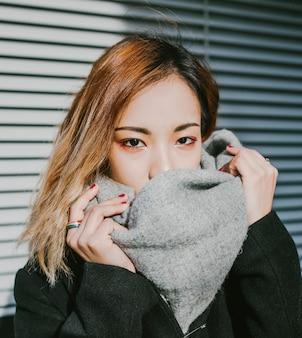 Aparência de menina asiática fecha o rosto do lenço