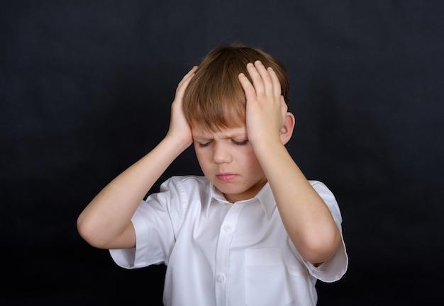 Aparência de menino europeu segurando sua cabeça com dor. conceito de dor de cabeça. isolar em um preto