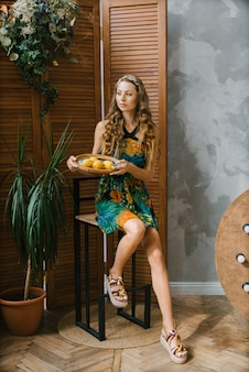 Aparência do modelo de uma jovem mulher vestida com um vestido de verão ou vestido, segurando um prato de limões