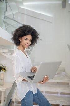 Aparência elegante. jovem sorridente e elegante mulata com laptop em pé na escada em uma sala iluminada