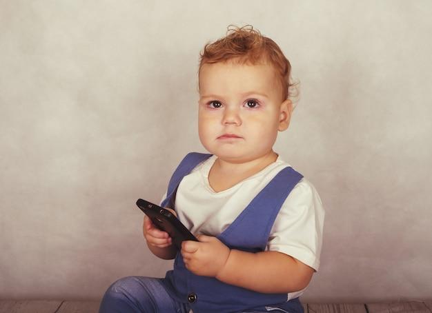 Aparência europeia do bebê brincando com o smartphone da mãe