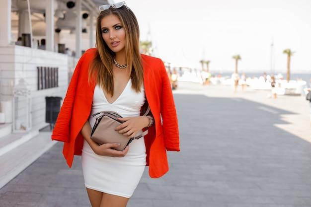 Aparência fashiom de verão. mulher loira sedutora com jaqueta vermelha e vestido branco posando perto da beira-mar.