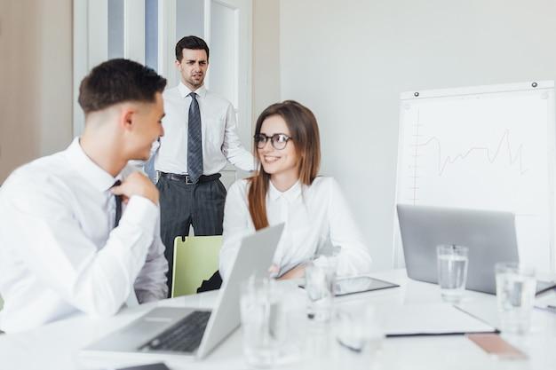 Aparição inesperada de um diretor em uma reunião de negócios em uma moderna sala de conferências