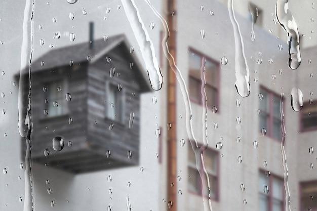 Apartamento branco pela janela com gotas de chuva