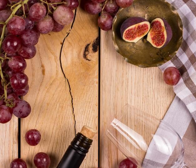 Apartamento com uma tempestade de uvas vermelhas, uma garrafa de vinho, um copo e figos