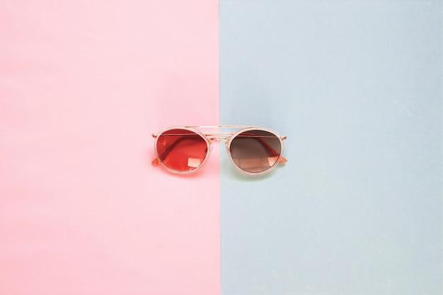 Apartamento criativo leigos de óculos de sol da moda em fundo de tom de cor pastel.