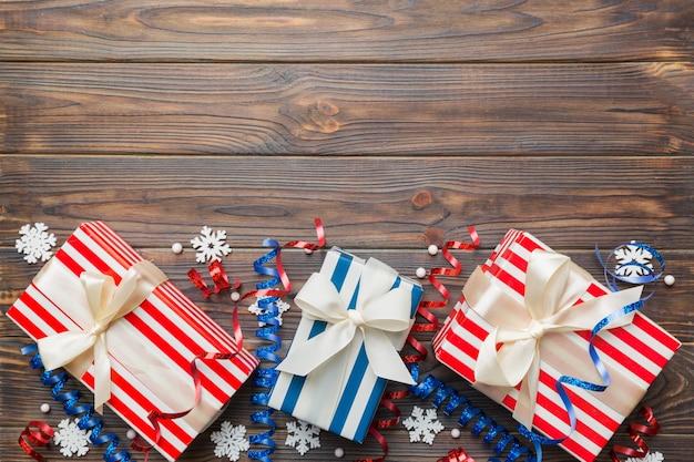 Apartamento de férias com caixas de presente embrulhadas em papel colorido e amarradas decoradas com confetes em fundo colorido. natal, aniversário, dia dos namorados e conceito de venda, vista superior.